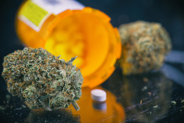 Cannabis buds and prescriptions pills over reflective surface -