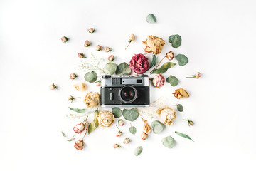 Flat lay, top view vintage retro photo camera, beige roses and green leaves on white. Blog hero