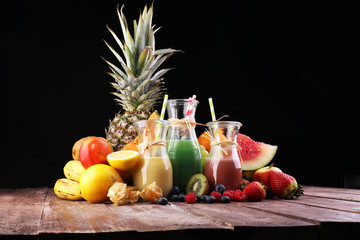 several bottles with fruit and berry juices smoothies and milkshakes , vintage wooden background, selective focus
