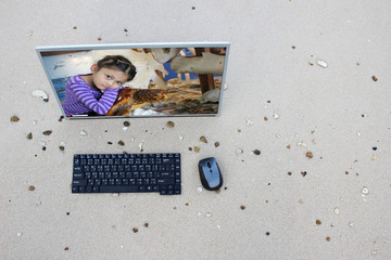 Computer on the beach with Asian girl and sea turtles on the screen,Marine conservation concept