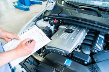 Mechaniker kontrolliert Auto mit Checkliste in Kfz-Werkstatt