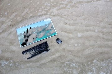 The computer on a beach with a hand images on the screen.Marine Conservation concept.