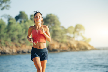 young healthy lifestyle woman running on beach