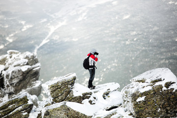 Hiker standing on a rock. Winter landscape. Shot of a young hiker taking photos from the top of a mountain