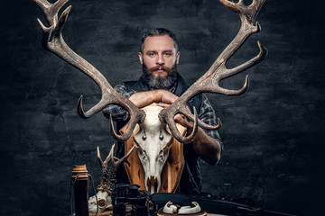 Portrait of hunter man holds a deer's skull.