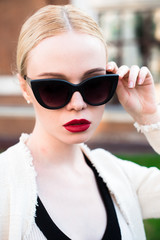 Happy Fashion blonde european elegant Woman with red lips and white skin Standing at the Old Red Brick building on green grass.  Beautiful Female in formal black and white dress wearing sunglasses.
