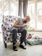 Young man relaxing in home with his dog. White boxer dog.