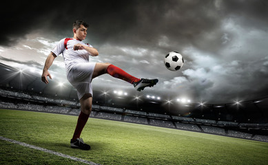 Football player is kicking a ball in the stadium.