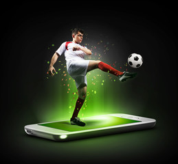 The football player in action on the phone, mobile football concept.