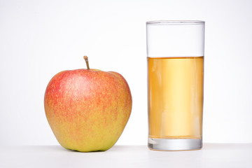 Glass of apple juice and an apple on white background