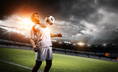Football player withstand a ball with his chest in the stadium