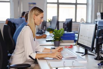 angestellte arbeiten am computer in einem großraumbüro