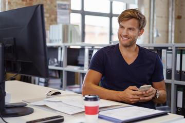 mann im büro mit computer und mobiltelefon