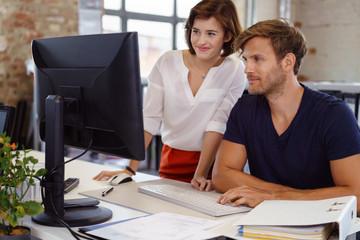 team im büro schaut gemeinsam auf computer