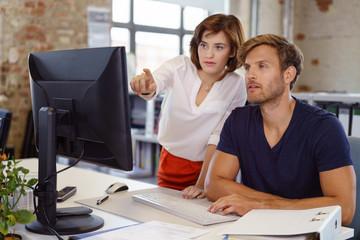 frau im büro erklärt einem kollegen etwas am computer