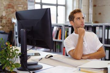 nachdenklicher junger mann am arbeitsplatz