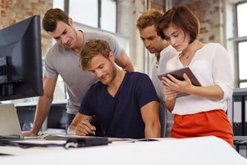 junge mitarbeiter mit computer und tablet in einer besprechung