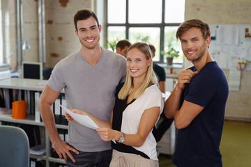 motivierte junge mitarbeiter stehen zusammen im büro