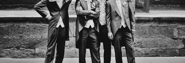 Groom with stylish groomsmen together at street
