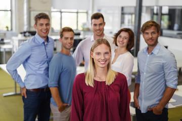 lächelnde blonde frau mit einem team im büro