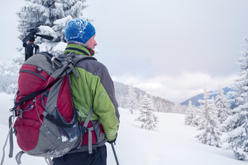 Man with backpack in snow covered forest