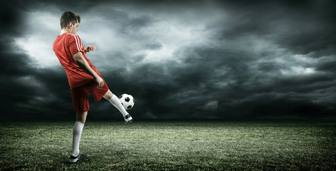 Football player is kicking a ball