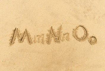 alphabet letters handwritten in sand on beach