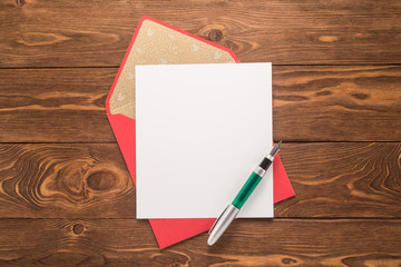 Blank paper, envelope and pen on a wooden background