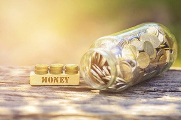 MONEY WORD Golden coin stacked with wooden bar on shallow DOF