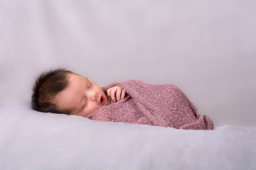 Beautiful newborn baby girl swaddled in a knit wrap