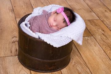Beautiful newborn baby girl asleep in a bucket