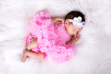 Beautiful newborn baby girl wearing a pink fluffly dress