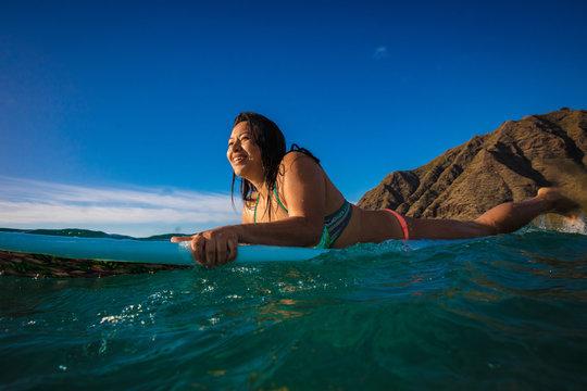 Hawaiian surfer girl in water on her surfing board