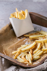 Fast food french fries potatoes with skin served with salt in lunch box on baking paper in old rusty oven tray with kitchen towel over gray texture background. Space for text
