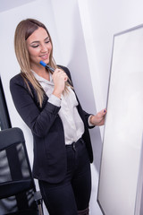 Thinking about today agenda. Business women ready for work. Woman holding a marker about to write on a marker board.