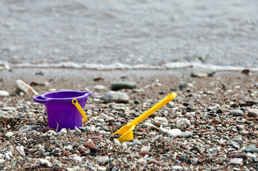 Lavender little baby toy bucket and spade on a pebble beach.