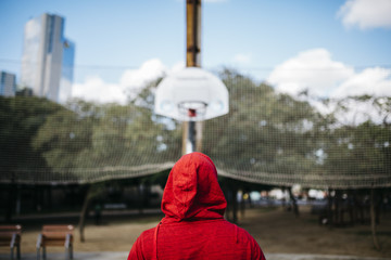 Young man wearing red hoodie on a basketball court