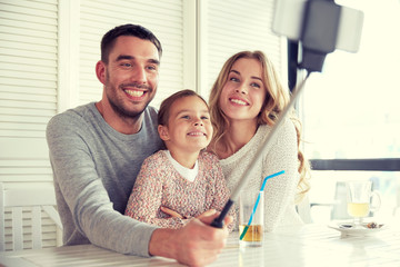 happy family taking selfie at restaurant