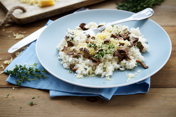 Risotto with wild mushrooms, parmesan and thyme on wooden texture background