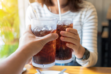 Men and Woman hand giving glass of cola.Glass of cola ,Soft drin