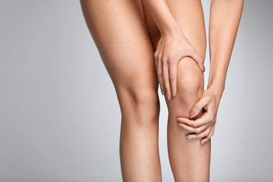 Pain In Knee. Closeup Of Female Leg With Painful Feeling In Knee