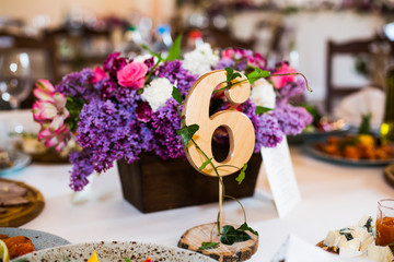 Wooden number 6 stands before box with violet flowers on dinner