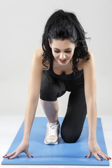 beautiful slim woman doing stretching exercises on yoga mat isol