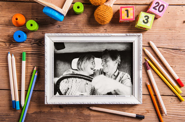 Black-and-white photo of senior couple in a car in white picture