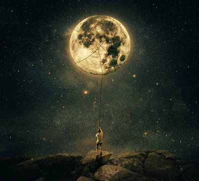 Imaginary view as a young man, holding a rope, try to catch and pull the full moon from the night sky. Achievement and hard determination concept.