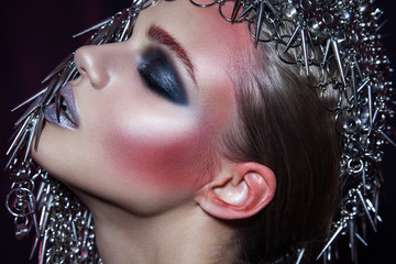 fashion beauty model with metallic headwear and shiny silver red makeup and blue eyes and red eyebrows on black background