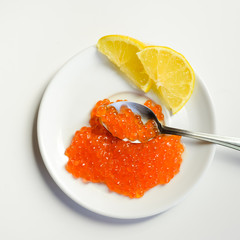 Red caviar with spoon and lemon on white background. Close up image of delicacy food luxury lifestyle