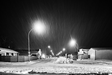A long line of snow plowed down the centre of small town main street lined with stores at night in black and white
