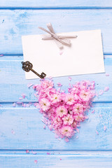 Heart from  pink  flowers and petals, empty tag  and vintage key
