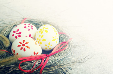Easter eggs with bright tapes in a nest on a linen background